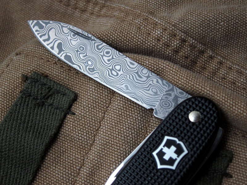 A Victorinox black Alox Pioneer featuring a main blade made of Damascus steel with a rated hardness of 60HRc. This edition was limited to 2010 knives world-wide.