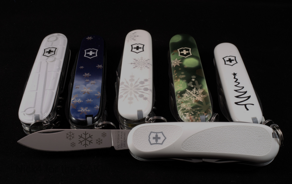 "Victorinox Christmas Series. Top line from left to right: Climber White Christmas 2015, Climber Christmas Knife ""Make a Wish"" Special Edition 2016, Explorer White Christmas Special Edition 2017, Climber Christmas Knife ""All your wish for"" Special Edition 2018, Sportsman White Christmas Special Edition 2018, Bottom line - Evolution White Christmas Special Edition 2016."